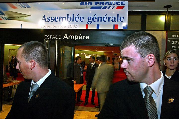 Des agents de sécurité surveillent l'entrée de l'assemblée générale d'Air France au Cnit de la Défense (Hauts-de-Seine), le 25 septembre 2002. (MARTIN BUREAU / AFP)