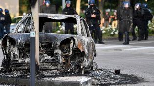 Des gendarmes se trouvent près d'une voiture brûlée à Dijon (Côte-d'Or), le 15 juin 2020,alors que la ville est secouée pour le troisième jour consécutif par des troubles imputés à des Tchétchènes cherchant à venger l'agression d'un adolescent. (PHILIPPE DESMAZES / AFP)