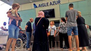 Des passagers attendent près du comptoir de la compagnie Aigle Azur à l'aéroport d'Alger, le 6 septembre 2019. (STRINGER / AFP)
