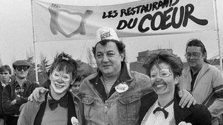Le 21 décembre 1985, Coluche pose avec deux femmes déguisées en clown devant l'un des trois restaurants des Restos du coeur en région parisienne  (MICHEL GANGNE / AFP)