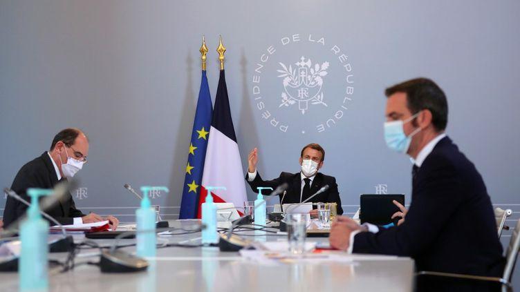 Le président Emmanuel Macron (milieu), avec le ministre de la Santé Olivier Véran (droite) et le Premier ministre Jean Castex, lors d'un Conseil de défense sanitaire, le 12 novembre 2020 à l'Elysée. (THIBAULT CAMUS / AFP)