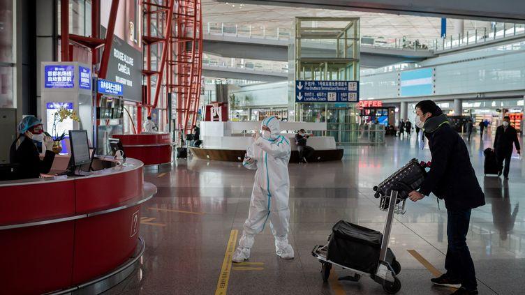 Un passager demande des informations aux employés de l'aéroport de Pékin (Chine), le 16 mars 2020. (NICOLAS ASFOURI / AFP)