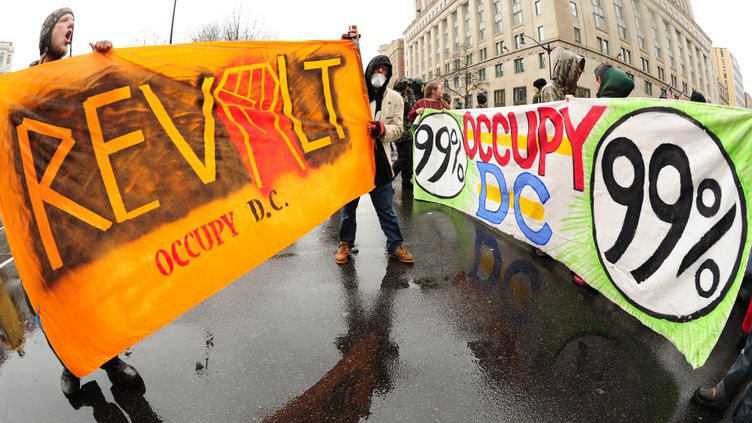 """Des manifestants du mouvement Occupy DC bloquent une rue à Washington au cours d'une série d'actions pour """"reprendre le Capitole"""", le 7 décembre 2011. (KAREN BLEIER / AFP)"""