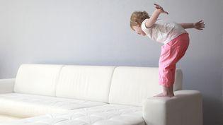 Une enfant s'apprête à plonger sur un canapé. (PHILIPPE TURPIN / PHOTONONSTOP/ AFP)