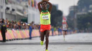 L'EthiopienFeyisa Lilesa franchit la ligne d'arrivée du marathon aux Jeux olympiques de Rio (Brésil), le 21 août 2016. (OLIVIER MORIN / AFP)