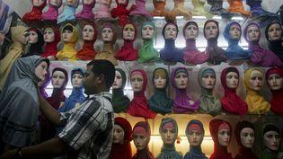 Un vendeur de foulards islamiques habille un mannequin sur son stand du marché de Banda Aceh (Indonésie), le 23 octobre 2012. (HERI JUANDA / AP / SIPA)