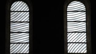 Les vitraux de Pierre Soulages vus de l'intérieur de l'abbaye de Sainte-Foy à Conques, en Midi-Pyrénées. (REMY GABALDA / AFP)