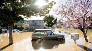 Une voiture repose dans les eaux de crue à San José, en Californie, le 22 février 2017. Des milliers de personnes ont dû évacuer leurs domiciles le mercredi précédent à cause des inondations. (NOAH BERGER / AFP)