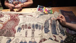 """Des couturières apportent les dernières touches à la tapisserie inspirée de """"Game of Thrones"""", à Belfast, le 5 juillet 2019 (PAUL FAITH / AFP)"""