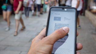Un touriste montre son pass sanitaire à Guérande (Loire-Atlantique), le 20 juillet 2021. (BAPTISTE ROMAN / HANS LUCAS / AFP)