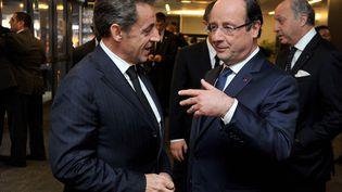 François Hollande et Nicolas Sarkozy échangent, le 10 décembre 2013, en marge de l'hommage consacré à Nelson Mandela, à Johannesbourg (Afrique du Sud). (ELMOND JIYANE / GCIS / AFP)