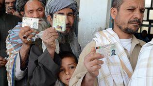 Des Afghans montrent leurs cartes d'identité avant de voter pour le scrutin présidentiel à Kandarah, le 5 avril 2014. (BANARAS KHAN / AFP)