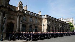 Plusieurs centaines de pompiers patientent devant l'Elysée avant la cérémonie en leur honneur, jeudi 18 avril à Paris. (LIONEL BONAVENTURE / AFP)