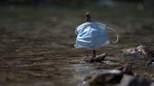 Un petit bateau fait de morceaux de bois,avec pour voile un masque chirurgical, flotte sur un cours d'eau à Briançon (Hautes-Alpes), le 23 avril 2021. (THIBAUT DURAND / AFP)