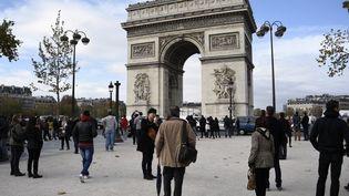 Des touristes au pied de l'Arc de Triomphe, à Paris, le 13 novembre 2015. (FRANCK FIFE / AFP)