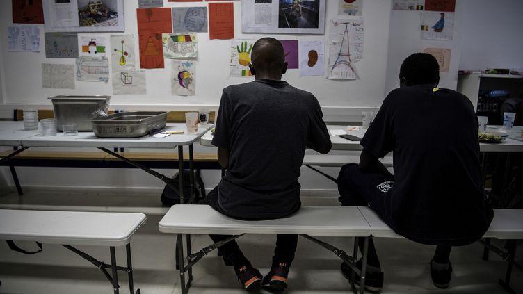 Des migrants prennent un repas dans un centre pour les migrants mineurs isolés, le 3 juillet 2018, à Pantin (Seine-Saint-Denis). (CHRISTOPHE ARCHAMBAULT / AFP)