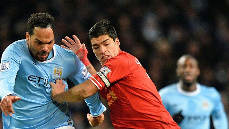 Joleon Lescott et Luis Suarez au duel lors du match aller entre Manchester City et Liverpool (2-1). (PAUL ELLIS / AFP)