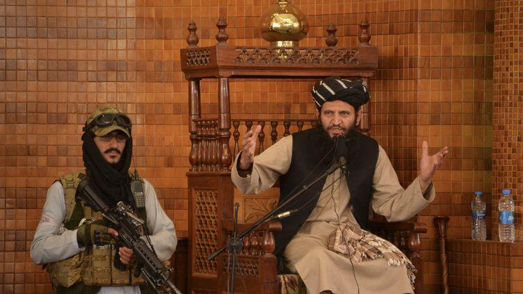 Un imam s'exprime aux côtés d'un combattant taliban lors de la prière du vendredi à la mosquée Abdul Rahman de Kaboul le 20 août 2021. (HOSHANG HASHIMI / AFP)