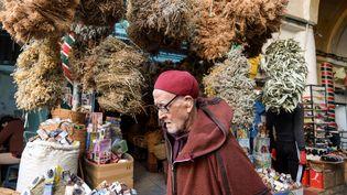 Vieil homme marchant à côté d'un commerce de plantes médicinales dans le souk el-Blat, dans la vieille ville de Tunis, le 14 mars 2020. (FETHI BELAID / AFP)