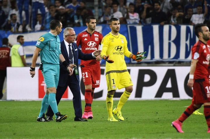 Le gardien de l'Olympique lyonnais avec des bouteilles ramassées autour de ses buts, lors du match opposant son équipe à l'Olympique de Marseille. (FRANCK PENNANT / AFP)