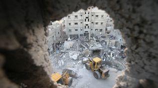 Des bulldozers déblayant les débris d'une maison de Rafah, dans le sud de Gaza,frappée par un tir israélien, le 11 juillet 2014. (IBRAHEEM ABU MUSTAFA / REUTERS)