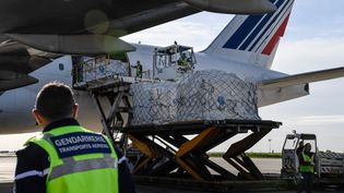 Des employésde l'aéroport Charles de Gaulle à Roissy déchargent des masques en provenance de Chine sur le tarmac, le 30 avril 2020. (BERTRAND GUAY / AFP)