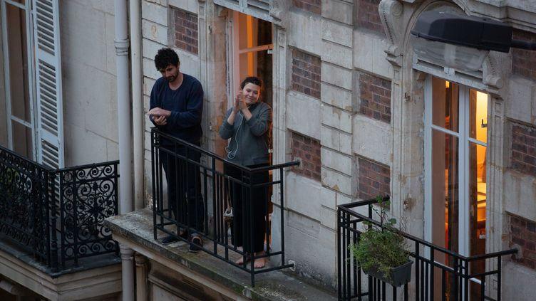 Des Parisiens à leur balcon pendant le confinement, en mars 2020. (MATTHIEU DE MARTIGNAC / MAXPPP)