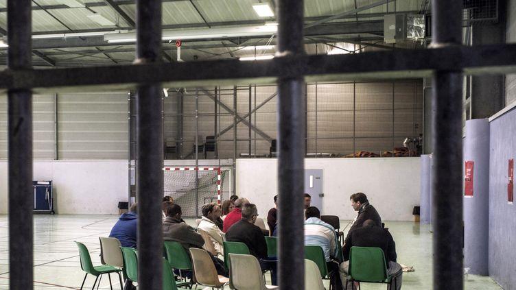 L'auteur français de romans noirs Olivier Truc présente son livre à des détenus le 29 mars 2013.  (JEFF PACHOUD / AFP)