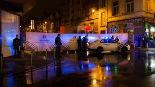 La police belge clôt, le 14 novembre, une rue du quartier de Molenbeek, à Bruxelles (Belgique), où résidaient plusieurs personnes suspectées d'avoir participé aux attaques du 13 novembre à Paris. (JAMES ARTHUR GEKIERE / AFP)
