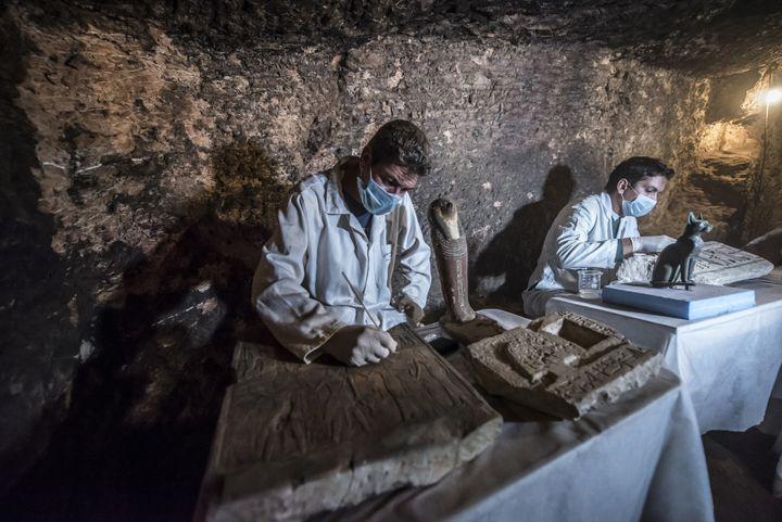 Sur le site de Saqqara, les arcjhéologues nettoient les statues et autres objets découverts dans les tombes.  (KHALED DESOUKI / AFP)