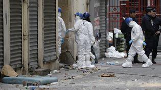 Des membres de lapolice technique et scientifique devant l'entrée de l'appartement où a été donné l'assaut le 18 novembre 2015 à Saint-Denis (Seine-Saint-Denis). (KENZO TRIBOUILLARD / AFP)