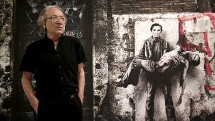 """Ernest Pignon-Ernest posant devant l'une des ces célèbres créations """"Pasolini"""". Ici lors d'une exposition au Mamac de Nice en 2016. (FRANCK FERNANDES / MAXPPP)"""