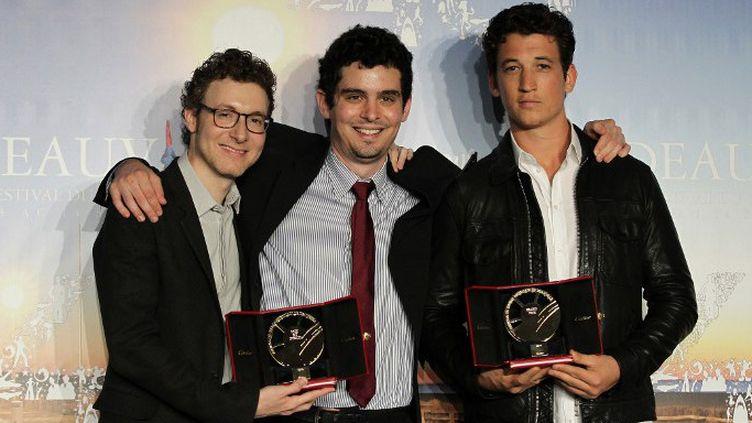 """Le réalisateur Damien Chazelle (C), le compositeur Nicolas Britell (G) et l'acteur Miles Teller (D), l'équipe de """"Whiplash"""" avec leurs Grand prix et le Prix du public, au 40e Festival du cinéma américain de Deauville, le 14 septembre 2014  (CHARLY TRIBALLEAU / AFP)"""