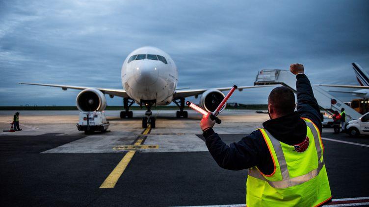 Un employé de l'aéroport de Roissy Charles de Gaulle guide l'arrivée d'un avion de ligne. Photo d'illustration. (MARTIN BUREAU / AFP)