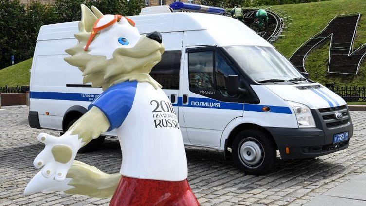 La mascotte de la Coupe du monde de football 2018, dépassée par une voiture de police à Moscou le 6 juin 2018. (KIRILL KUDRYAVTSEV / AFP)
