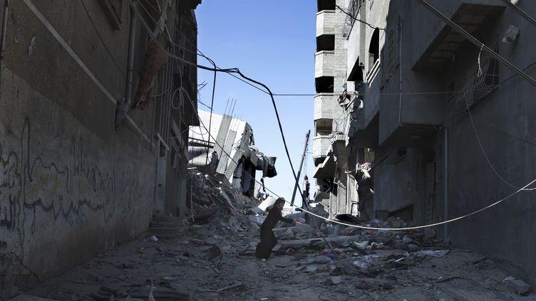 Une Palestinienne court pour tenter de se mettre à l'abri des bombes à Gaza, le 27 juillet 2014. (© FINBARR O'REILLY / REUTERS / X90055)