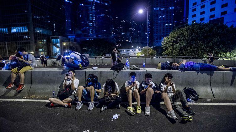 Des manifestants pro-démocratie consultent leur téléphone, à Hong Kong, le 29 septembre 2014. (XAUME OLLEROS / AFP)