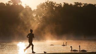 Une femme fait un footing autour d'un étang. (DANIEL LEAL-OLIVAS / AFP)