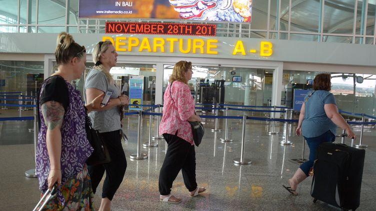 Des touristes se renseignent sur les vols à l'aéroportNgurah Rai de Bali (Indonésie), le 28 novembre 2017. (ANTARA FOTO AGENCY / REUTERS)