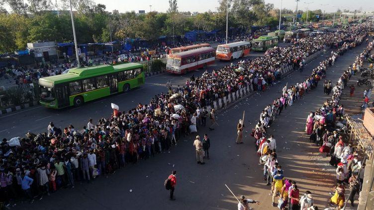 Des milliers de travailleurs migrants tentent de prendre le bus pour rejoindre leur village pendant le confinement, le 28 mars 2020 à New Delhi (Inde). (BHUVAN BAGGA / AFP)