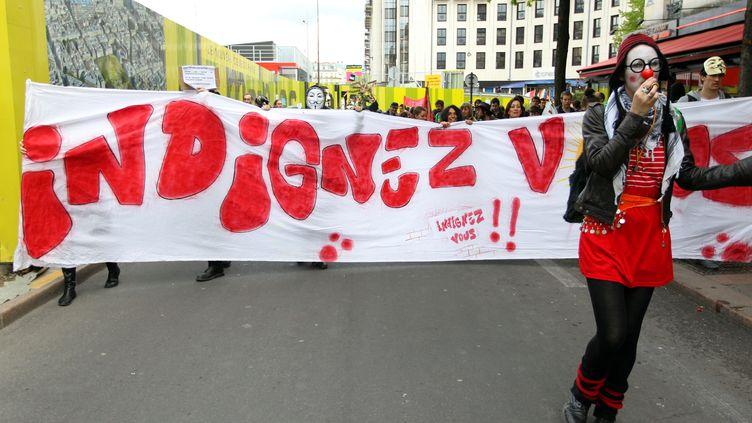 Des manifestants défilent le 21 avril 2012 à Paris, avec une banderole marquée du titre de l'ouvrage de Stéphane Hessel. (KENZO TRIBOUILLARD / AFP)