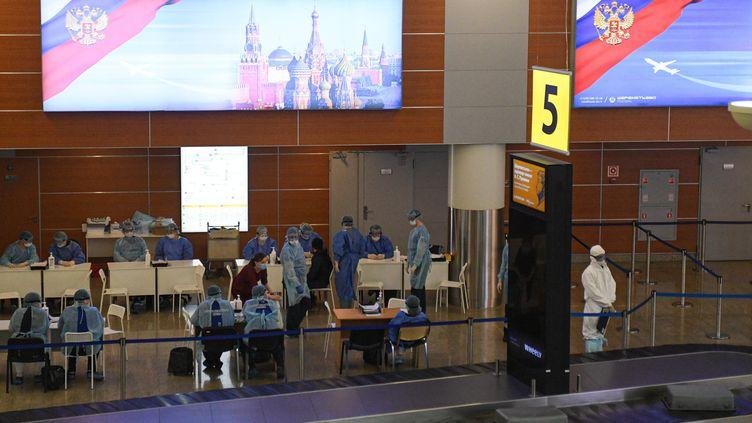 Des médecins russes portent des tenues de protection pour examiner les passagers à l'aéroport international de Moscou (Russie), le 26 mars 2020. (GRIGORY SYSOEV / SPUTNIK / AFP)