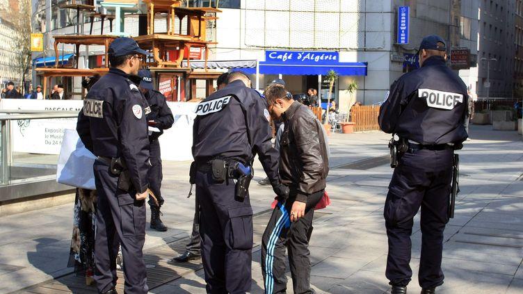 Des policiers procèdent à un contrôle d'identité à Lyon (Rhône), le 22 mars 2011. (JUSTE PHILIPPE / MAXPPP)