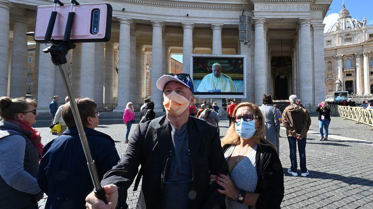 Un couple se prend en photo pendant la prière de l'Angélus du pape François sur la place Saint-Pierre à Rome (Italie), le 8 mars 2020. (ALBERTO PIZZOLI / AFP)