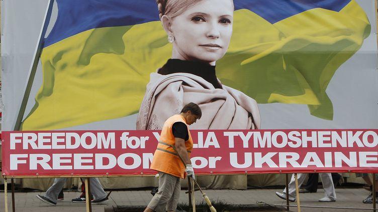 Un balayeur passe devant une affiche représentant l'opposante Ioulia Timochenko dans les rues de Kiev, le 1er juin 2012. (REUTERS)