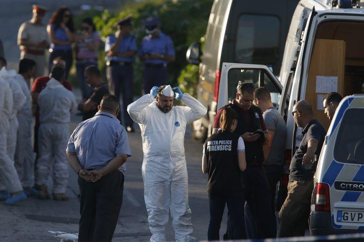 Des policiersont examiné les preuves matérielles, sur la route et dans le champ où a été retrouvée la carcasse du véhicule. (DARRIN ZAMMIT LUPI / REUTERS)