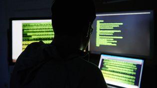 Une personne travaille des lignes de code sur trois écrans d'ordinateur, le 16 juillet 2019 à Berlin (Allemagne). (ANNETTE RIEDL / DPA)