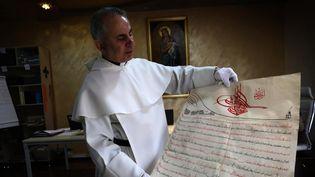 Le père Najeeb Michaeel et un de ses précieux documents  (SAFIN HAMED / AFP)