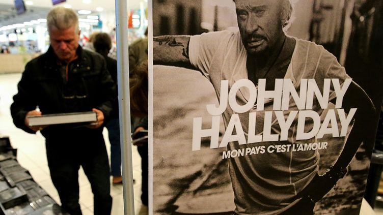 """Promotion de l'album posthume de Johnny Hallyday """"Mon pays c'est l'amour"""", le 19 octobre 2018 dans un supermarché de Reims. (FRANCOIS NASCIMBENI / AFP)"""