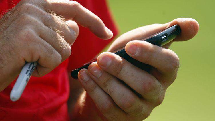 Le golfeur Ian Poulter utilise son téléphone pendant le championnat PGA sur le parcours duHazeltine National Golf Club, dans le Minnesota (Etats-Unis), le 11 août 2009. (SCOTT HALLERAN / GETTY IMAGES NORTH AMERICA / AFP)